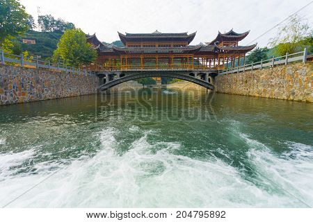 Low angle view of the traditional wooden bridge at Xijiang Miao ethnic minority village in Guizhou China