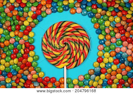 Colorful sweets and lollipops on blue background, top view