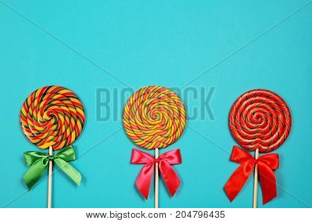 Three lollipops on blue background, top view