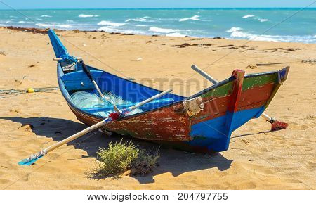 the fishing boat with network and oars costs on the beach of the Persian Gulf