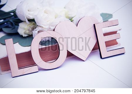 Wooden love letters inscription with heart shape. Vintage style with white flowers.