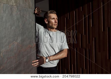 Handsome adult man wearing casual t-shirt leaning on wall and looking away.