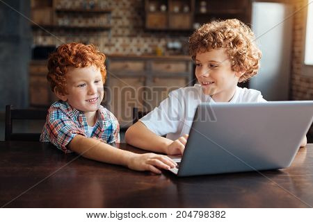 Harmonious relations. Mindful older boy looking at his little brother reaching the keyboard of his computer while both sitting in the kitchen and enjoying their time spent together.