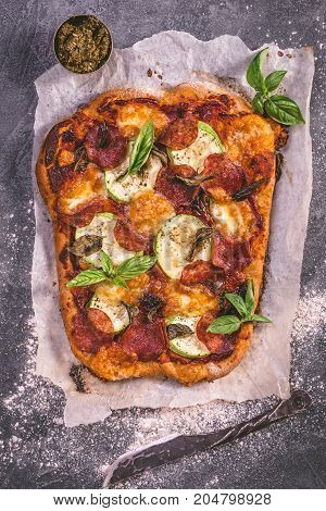 Rustic spicy salami, courgette and  mozzarella pizza with basil. Top view