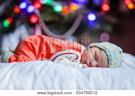 One week old newborn baby near Christmas tree with colorful garland lights on background. Closeup of cute child, little baby looking at the camera. Family, Xmas, birth, new life concept