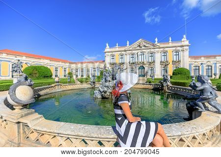 Tourism in Europe. Elegant woman sitting in front of Queluz National Palace or Royal Palace of Queluz and Neptune Fountain in Sintra, Lisbon. Female tourist enjoys a trip to popular city of Sintra.
