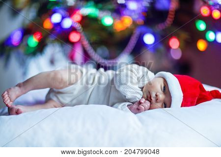 One week old newborn baby in Santa hat near Christmas tree with colorful garland lights on background. Closeup of cute child, little baby looking at the camera. Family, Xmas, birth, new life concept