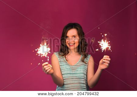 Young woman having fun with a sparkler