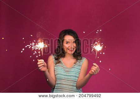 Portrait of young attractive celebrating woman holding sparklers.