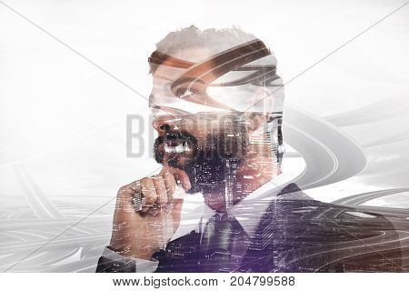Double exposure of a thoughtful businessman with complex road and skyscrapers