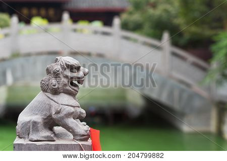 Lion stone statue in a chinese buddhist temple with a birdge in the background, Chengdu, China