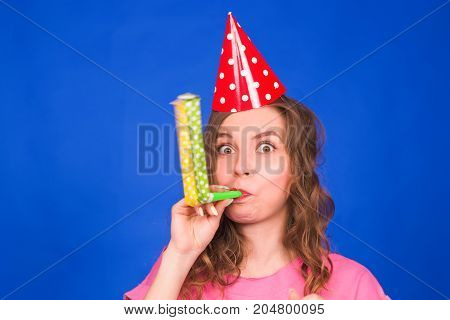 Young woman blowing two party whistles against blue background