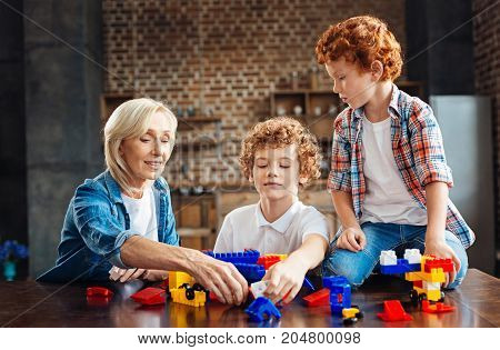 Total peace and understanding. Cheerful elderly lady taking a plastic toy block while sitting next to her male grandchildren and talking to them
