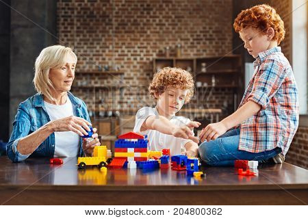 Children are the rainbow of life. Mindful grandmother looking at her grandkids while all sitting at a table and playing with a set of colorful plastic toy building blocks.
