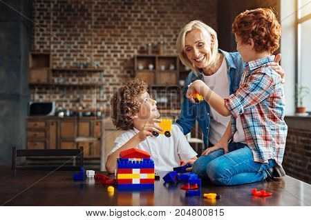 Look what we built. Joyful elderly lady grinning broadly while embracing her grandsons while they playing with a construction set and showing her cars built by themselves.