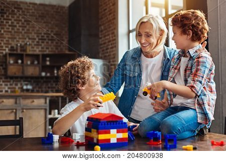 Family is a little word created by love. Positive minded grandmother looking at her grandkids with eyes full of love while embracing them