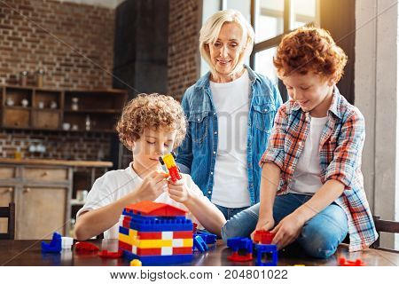 I am so proud of them. Selective focus on a cheerful grandmother standing next to her grandsons and looking at them while they playing with a construction set and building a house