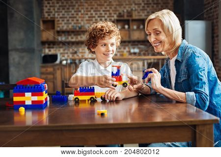 Best friends forever. Adorable moment of an excited elderly woman grinning broadly while spending some time with her grandchild and playing with a construction set together.