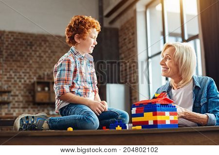 Love is in the air. Side view on a positive minded elderly woman chatting with her adorable smiling grandchild while both getting creative and playing with colorful building blocks at home.