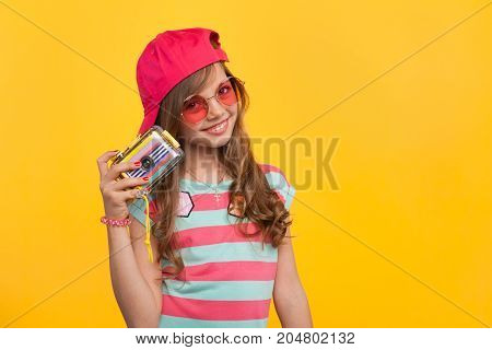 Young charming hipster girl in sunglasses and cap posing with colorful photo camera on orange background.