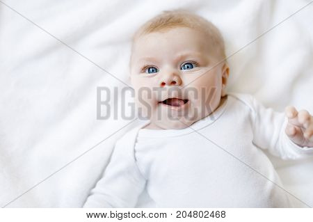 Baby girl with blue eyes wearing white towel or blanket in white sunny bedroom. Newborn child relaxing in bed. Nursery for children. Textile and bedding for kids. Happy cute new born girl or boy