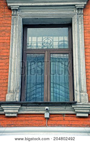 An old window with a lattice on a brick wall of an apartment house