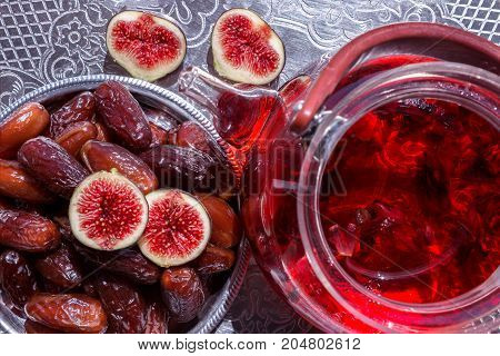 Hibiscus (karkade) tea in transparent teapot on a silver tray. Appetizer of sweet dates and ripe figs slices.