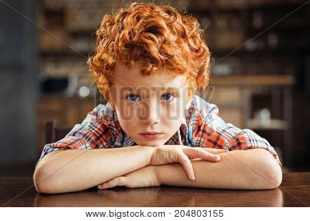 Not in the mood today. Portrait of a moody redhead boy leaning on a dining table and looking into the camera with eyes full of sadness at home.