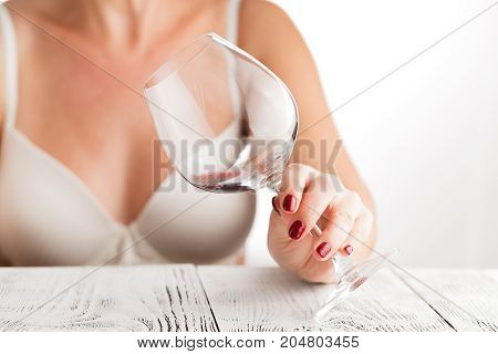 Beautiful Woman Appreciating A Glass Of Red Wine As She Looks Down At The Glass Tilted In Her Hands