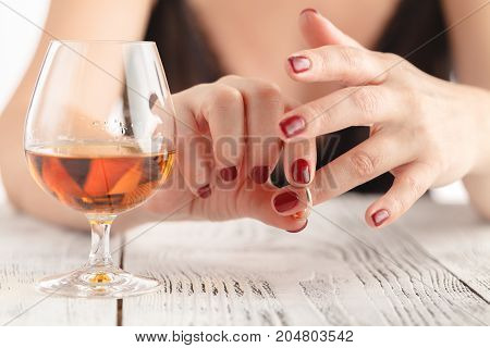 Woman Take Off Wedding Ring And Drink Whiskey On Wooden Table