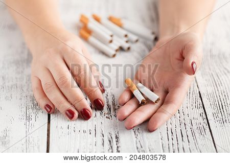 woman hand breaking cigarette over white background