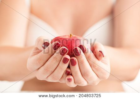 Young Woman Holding Red Apple In Hand. Girl With Red Apple In Hand On White Background