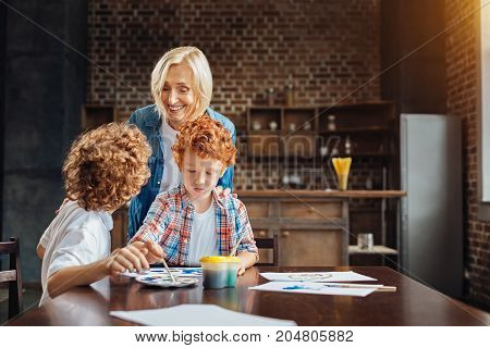 Grandma did you know. Positive mature woman joining her grandchildren painting with watercolors and grinning widely while listening to one of them telling her a story.