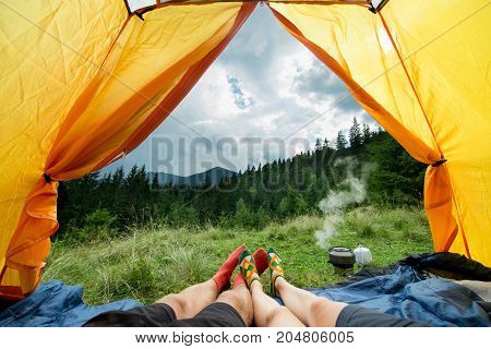 legs of a couples of man and woman in a tent outdoors
