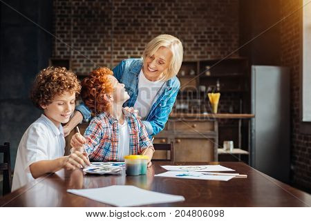 Love and harmony. Mindful elderly lady touching shoulders of her grandsons while watching them painting and chatting with her at a table.