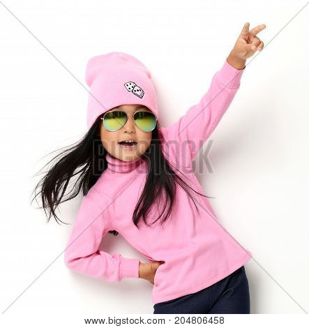 Happy young little child girl gesturing keeping hand raised and expressing positivity looking at the camera in pink headband and sunglasses on white background