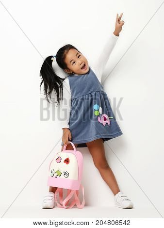 Happy young little child girl with backpack first class gesturing keeping hand raised up and expressing positivity on white background