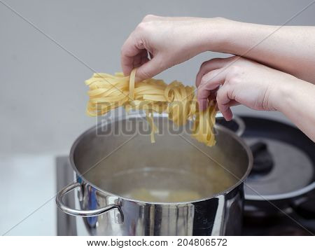 Female hands about to drop spaghetti into a boiling water the steam coming out of casserole