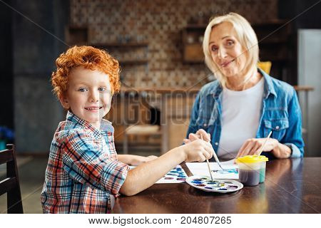 We have so much fun together. Selective focus on a cute redhead kid turning and posing for camera with an excited smile on his face while painting with his loving grandmother at home.