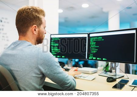 Portrait of young handsome programmer working in office