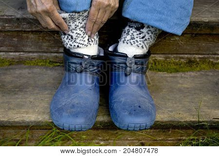 Woman putting warm socks while sitting on the wooden steps closeup cropped photo
