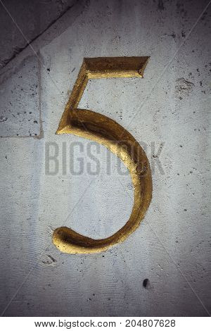 Carved golden number five on weathered white wall