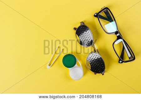 A set of accessories for sight. Pinhole glasses lenses with container and glasses for sight. Pair of medical pinhole glasses with reflections. Medical concept. Top view.