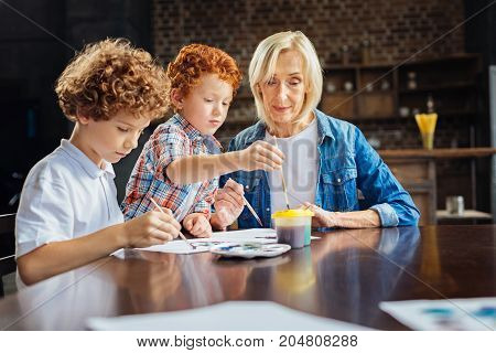 Harmonious family relations. Adorable shot of mindful senior lady spending weekend with his two adorable grandsons and watching them painting with watercolors