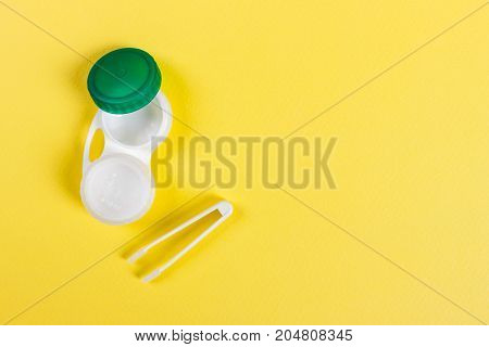 Container for contact lenses tweezers yellow table
