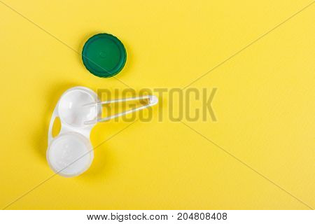 Accessories for contact lenses: container tweezers Yellow background