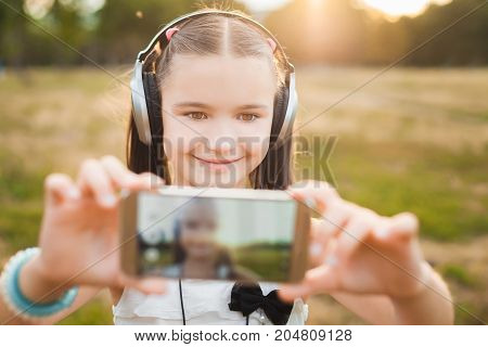 happy girl making selfie on nature, cute child with black and silver headphones listening music and making selfie on smartphone