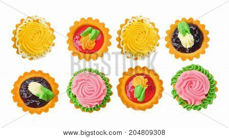 Two Rows of Delicious Little Tarts with Colored Butter Cream Fruit Jam and Decoration isolated on White background. Top View