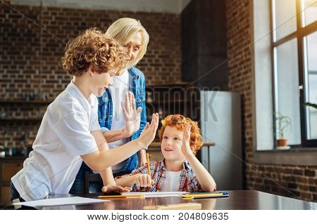 One for all and all for one. Adorable ginger haired boy giving a high fie to his granny and older brother while sitting at a table and drawing with colorful pencils.