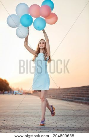 happy beautiful woman with flying multicolored balloons at sunset.